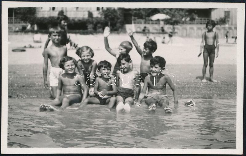 cca 1934 Kinszki Imre (1901-1945) budapesti fotóművész hagyatékából, jelzés nélküli vintage fotó (Strandon, az ülő sor bal szélén Kinszki Gáborka), 5x8 cm
