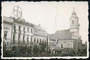1940 Kolozsvár, Bevonulás, utcarészlet a lutheránus templommal, a házakon nemzeti színű zászló, Bayer gyógyszerreklám, Biasini Sándor üzlete, fotó, felületén törésnyom, 5,5×8,5 cm
