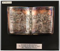 Ezüst (Ag) elnöki ajándék: Simon Peresz (1923-2016) izraeli elnök ajándékba Sólyom Lászó (1942- ) magyar köztársasági elnöknek Magyarországi látogatása során. Sólyom László elnöki ajándéktárgyainak jótékonysági árveréséről. Miriam Hirszowicz tervezte Biblia formájú ezüst (Ag) emléktárgy fa talapzaton, jelzett, talapzat: 18,5x16,5x3,5 cm, Biblia: 13,5x8 cm, bruttó: 1188 gr.